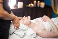 Целительные часы досуга Удовлетворенная женщина имея массаж стороны в спа-комплексе стоковые изображения