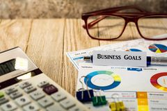 Цели бизнеса финансируют и концепция вклада с диаграммами и диаграммами на деревянной доске Стоковые Изображения
