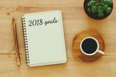 Цели взгляд сверху 2018 перечисляют с тетрадью, чашкой кофе на деревянном столе Стоковое Фото