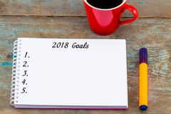 Цели взгляд сверху 2018 перечисляют с тетрадью, чашкой кофе на деревянном Стоковая Фотография