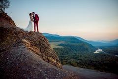 Целовать новобрачных на краю гор Чувствительный портрет во время захода солнца красивейшая природа Стоковая Фотография