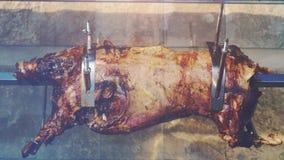Целый зажарило в духовке свинью на вертеле, вредной жирной пище, еде улицы, тучном капании от мяса, зажаренного свинины движение  акции видеоматериалы