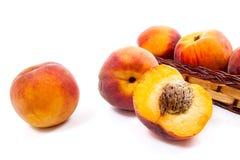 Целый и половина зрелого плодоовощ персика и несколько в изоляте корзины Стоковые Фото