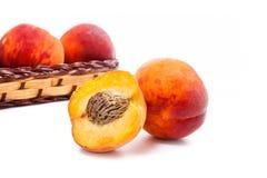 Целый и половина зрелого плодоовощ персика и несколько в изоляте корзины Стоковые Фотографии RF