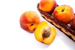 Целый и половина зрелого плодоовощ персика и несколько в изоляте корзины Стоковые Изображения RF