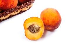 Целый и половина зрелого плодоовощ персика и несколько в изоляте корзины Стоковое Фото