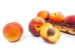 Целый и половина зрелого плодоовощ персика и несколько в изоляте корзины Стоковая Фотография RF
