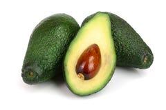 Целый и половинный авокадо изолированные на белом конце-вверх предпосылки Взгляд сверху Стоковое Изображение RF