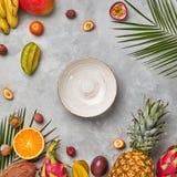 Целый и половины экзотических здоровых плодоовощей, карамболы, ананаса, маракуйи, pitahaya, листьев зеленого цвета ладони и пусто стоковое изображение rf