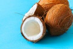 Целый и halfs кокосов на голубой предпосылке Взгляд сверху и c Стоковое Фото