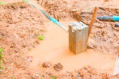 Цементируйте штендер в яме которая имеет воду и трубопровод в месте строительства стоковые изображения rf