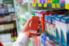 Цена сканирования аптекаря на красной коробке медицины с читателем штрихкода в магазине фармации стоковые фото