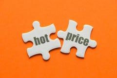 ЦЕНА слова ГОРЯЧЕЕ на соответствуя головоломке 2 на оранжевой предпосылке стоковые изображения rf