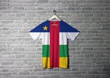 Центрально-африканский флаг на рубашке и висеть на стене с обоями картины кирпича стоковое фото