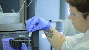 Центрифуга медицинской лаборатории Ученый женщины нагружает пробирки жидкости в центрифугу в лаборатории scientist акции видеоматериалы