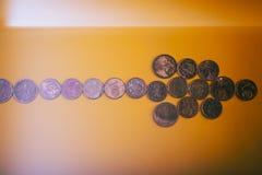 Центы евро монеток в форме стрелок лежат на желтом backgroun Стоковые Фотографии RF