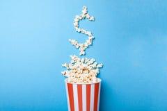 Цены билета концепции или кино кассы Разлитый попкорн в форме знака доллара от бумажного ведра в красной прокладке Стоковое Изображение