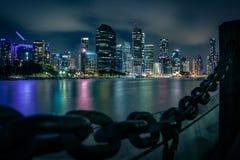 Цепи и город рельса подпирают около реки на ноче стоковая фотография rf