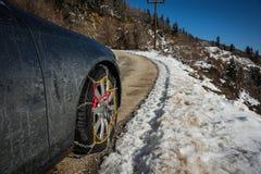 Цепи на weels автомобиля в снежных горах во время зимы стоковое фото rf