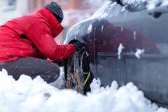 Цепи снега на колесах автомобиля Человек подготавливая автомобиль для путешествовать на зимнем дне стоковое изображение rf