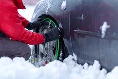 Цепи снега на колесах автомобиля человек пробует положить цепи снега на автошины схватывая цепи снега стоковое фото