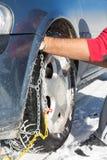 Цепи снега установки человека на колесах Стоковая Фотография