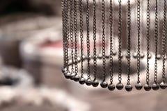 Цепи с колоколами висят в круге на предпосылке сумок специй стоковое фото rf
