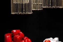 Цепи с колоколами в форме шариков выделены и висят над овощами на черной предпосылке стоковое фото rf