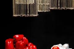 Цепи с колоколами в форме шариков выделены и висят над овощами на черной предпосылке стоковое изображение