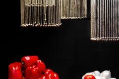 Цепи с колоколами в форме шариков выделены и висят над овощами на черной предпосылке стоковые изображения