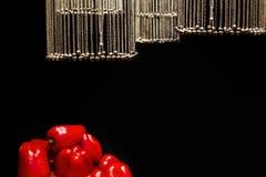 Цепи с колоколами в форме шариков выделены и висят над овощами на черной предпосылке стоковые фотографии rf