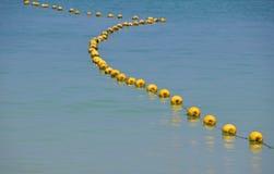 Цепь желтых томбуев в голубой морской воде Стоковые Фото
