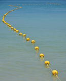 Цепь желтых томбуев в голубой морской воде Стоковое Изображение