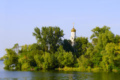 Церковь в деревьях на банке реки Стоковые Фотографии RF