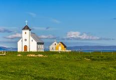 Церковь лютеранина Flateyjarkirkja белые и пары живущих хат Стоковое Фото