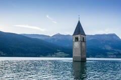 Церковь под водой, потопленной деревней, ландшафтом гор и пиками в предпосылке Озеро Reschen Lago di Resia Reschensee стоковые изображения rf