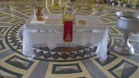 церковь правоверная подготовка для крещения ребенка с библией, вода, крест на таблице видеоматериал