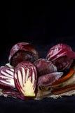 Целый и отрезок в половинной свежей красной капусте в деревянной плите на темной предпосылке Стоковые Фотографии RF