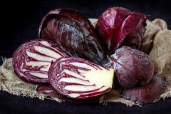 Целый и отрезок в половинной свежей красной капусте в деревянной плите на темной предпосылке Стоковые Изображения