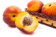 Целый и половина зрелого плодоовощ персика и несколько в изоляте корзины Стоковые Изображения