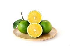 Целый и половинные сладкие апельсины на круглом деревянном подносе на белом backg Стоковые Изображения