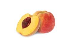 Целый и половинный персик при изолированный камень Стоковое Изображение