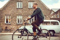Цикл катания молодого человека за историческими кирпичными зданиями в центре старого города стоковое фото