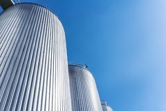 Цилиндры фабрики напитка С голубым небом стоковое изображение