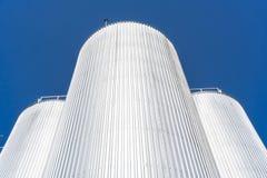Цилиндры фабрики напитка С голубым небом стоковые изображения rf