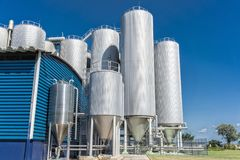 Цилиндры фабрики напитка С голубым небом стоковое фото