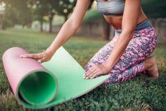 Циновка йоги завальцовки молодой женщины в парке Стоковая Фотография RF
