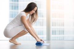 Циновка йоги молодой женщины разворачивая стоковое изображение