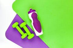 Циновка йоги Фиолетовые и зеленые разминки циновки 2 зеленых гантели Стоковые Фото