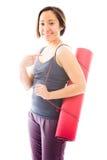 Циновка нося тренировки молодой женщины показывая что-то и усмехаться Стоковое фото RF
